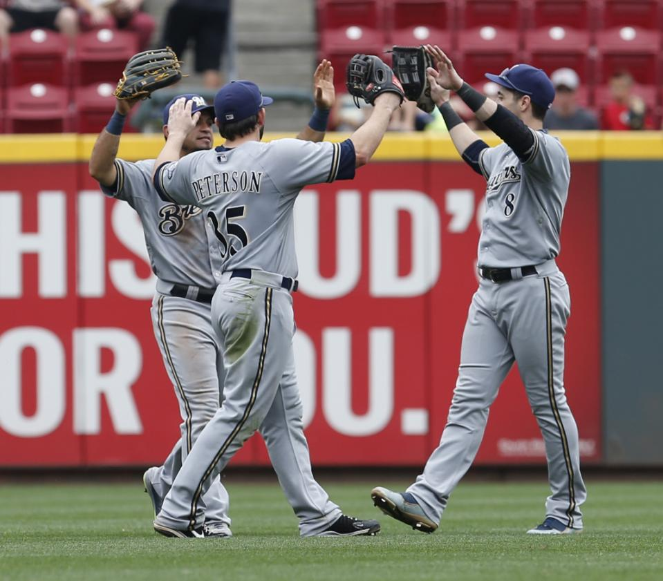 Milwaukee Brewers out fielders Shane Peterson (35), Gerardo Parra (28), and Ryan Braun (8) celebrate their 6-1 win over the Cincinnati Reds in a baseball game, Sunday, July 5, 2015, in Cincinnati. (AP Photo/Gary Landers)